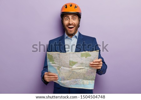Horizontal shot of happy male architect with map, studies location map where construction site is situated, wears protective helemt, formal wear, isolated on purple wall. Engineer with blueprint