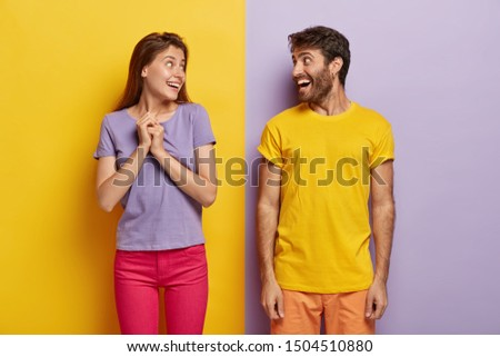 Horizontal shot of happy woman and man look gladfully at each other, dressed in vivid summer clothes, have fun, meet after departure, express positive emotions and feelings. Joyous couple indoor