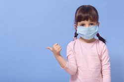 Horizontal shot of little girl dresses medical protective mask and rose shirt, posing in studio, pointing aside with thumb. Coronavirus, covid 19, quarantine concept. Copy space of advertisment.