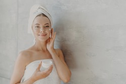 Horizontal shot of lovely female model applies moisturizer on face, holds jar of cosmetic cream has beauty treatment routine, wrapped in bath towel, poses against grey wall with bare shoulders