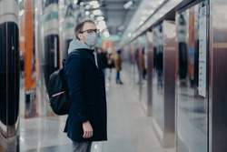 Horizontal shot of man traveler poses on metro station, wears medical mask during coronavirus time, waits for train, commutes to work by public transport. Virus, disease and influenza concept