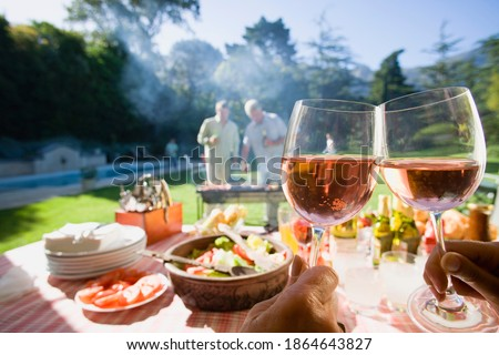 Fototapete Horizontal shot of men grilling food at a family barbecue in the summer garden with the focus on food and wine lying on the table in the foreground.