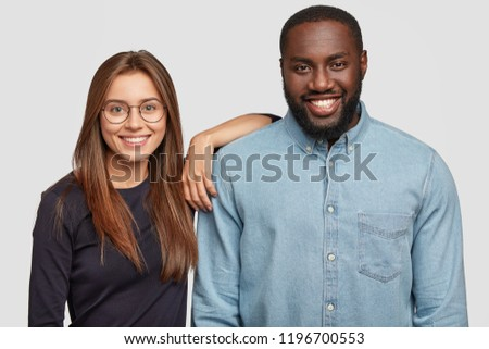 Horizontal shot of mixed race couple stand closely to each other, being in good mood, collaborate for common work, have good relationships, isolated over white background. Interracial partners