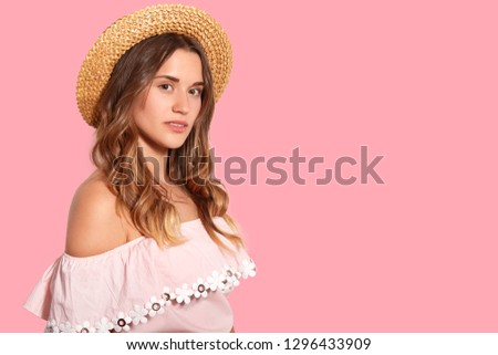 Horizontal shot of pleasant looking young woman stands bare shoulders, wears summer hat and fashionable blouse, thinks about somehting, isolated over pink background with free space for text #1296433909