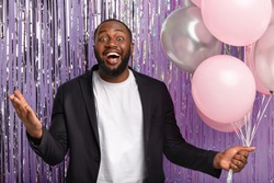 Horizontal shot of positive dark skinned man in black festive suit, holds balloons, gestures actively, stands over purple background, greets friends on anniversary party, expresses positive emotions