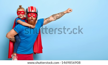 Horizontal shot of powerful man makes fly gesture, gives piggyback to small daughter dressed in superhero suit, have supernatural abilities, enjoy free time together. Real heroes defend you.