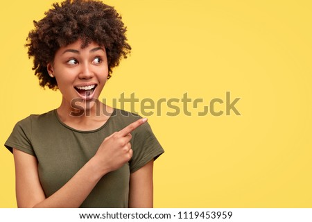 Horizontal shot of prettty young joyful African American female points with fore finger away, indicates copy space on blank wall, isolated over yellow background. Check this out. Ethnicity concept