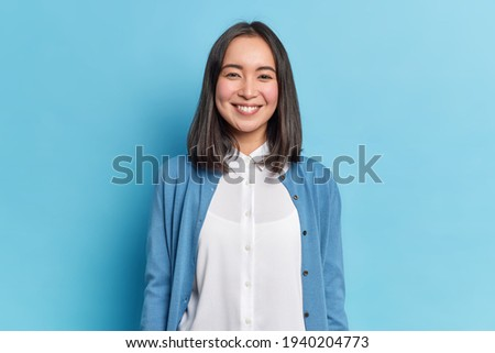 Horizontal shot of pretty Asian woman with dark hair smiles pleasantly looks directly at camera has toothy smile wears white shirt and jumper isolated over blue background. Emotions concept.