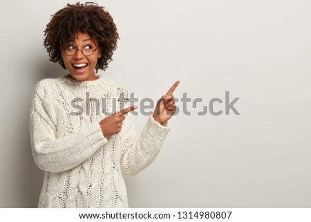 Horizontal shot of pretty happy dark skin woman with curly hair, wears loose sweater, points at white blank wall, pleased to visit this place, attracts your attention away. Ethinicity, advertisement