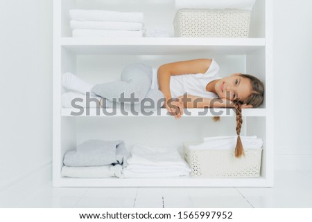 Horizontal shot of restful girl with pigtail lies on white console shelf, dressed in casual clothes, surrounded with piles of folded linen, basin of fresh laundry, has rest after helping mother