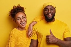Horizontal shot of satisfied dark skinned woman laughs happily, leans at shoulder of boyfriend, come together on theme party, dressed in yellow clothes. Pleased bearded Afro man shows thumb up