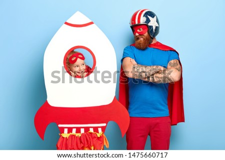 Horizontal shot of satisfied man wears headgear and red cape, keeps arms folded, looks at playful girl who looks through hole of rocket, prepare for flight, play together stand indoor. Happy childhood