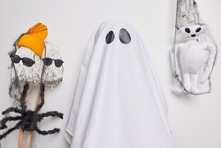 Horizontal shot of scary ghost stands indoor against creepy handmade creatures prepares for halloween wears spooky costume isolated over white background. Mysterious holiday inn autumn. Magic event