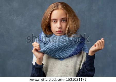 Horizontal shot of serious calm woman wears looks straightly at camera. Teenage girl with long thick blonde hair wearing warm woolen blue sweater and scarf is isolated against texture wall in Studio.