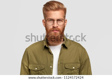 Horizontal shot of serious ginger stylish male has thick beard and mustache, dressed in green shirt, looks seriously at camera, ready to give consultancy to client, poses against white background