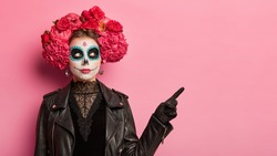 Horizontal shot of serious woman wears scary makeup spends free time on halloween party points away at copy space isolated over pink background celebrates traditional mexical holiday. Face art