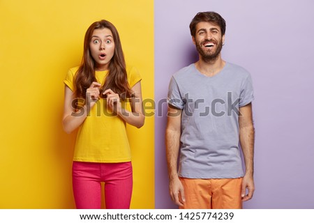 Horizontal shot of shocked beautiful woman hears shocking relevation, cheerful unshaven man rejoices good news. Family couple express different emotions. People, human facial expressions concept