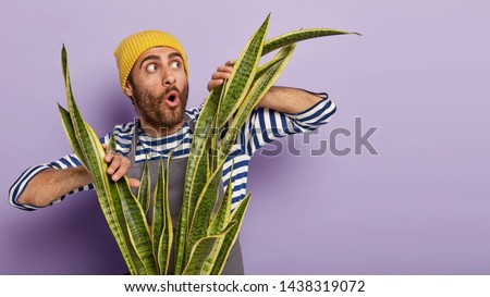 Horizontal shot of shocked botanist keeps mouth opened, gazes aside, stands in front of green houseplant, notices somethning unbelievable, poses over purple wall. Botany and housekeeping concept