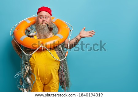 Horizontal shot of shocked embarrassed bearded male seafarer poses with inflated lifering fishing net smokes pipe raises hand over blue wall demonstrates copy space for your advertising content Stok fotoğraf ©
