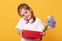 Horizontal shot of shy sweet lovely little girl smiling sincerely, looking directly at camera, holding red and white box, blue flowers, giving present, standing isolated over yellow background.