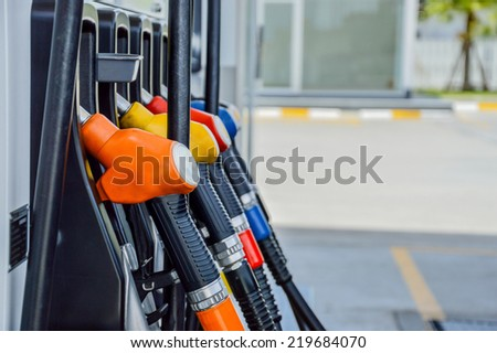 Horizontal shot of some fuel pumps at a gas station.