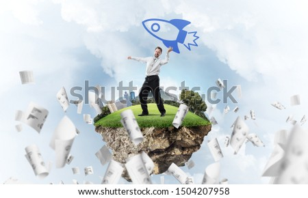 Horizontal shot of successful and young businessman, standing among flying papers on the flying island and throwing huge rocket in the air, with cloudy skyscape view on background. #1504207958