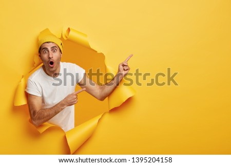 Horizontal shot of surprised young Caucasian man in white t shirt and yellow headgear, has widely opened mouth, indicates at copy space, models in torn paper background. Wow, just look there