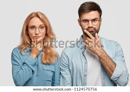 Horizontal shot of thoughtful male and female colleagues hold chins and being concentrated on solving problem, look directly into camera. Blonde middle aged female and her brother work as team