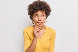 Horizontal shot of thoughtful young African American woman looks aside has dreamy expression interesting idea in mind wears casual yellow jumper isolated over white background makes decision