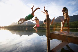 Horizontal shot of three adults jumping off a jetty into a lake as a girl in bikini cheers them with copy space.