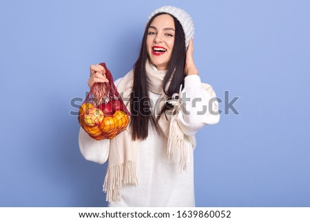 Horizontal shot of woman holding shopping bag full of apples and oranges, posing isolated over over blue background, lady dresses white clothes, looking smiling directly at camera with opened mouth.