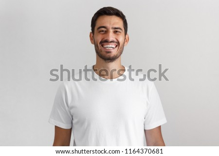 Horizontal shot of young positive european man isolated on gray background standing in blank white casual t-shirt looking straight at camera with happy smile, laughing Foto d'archivio ©