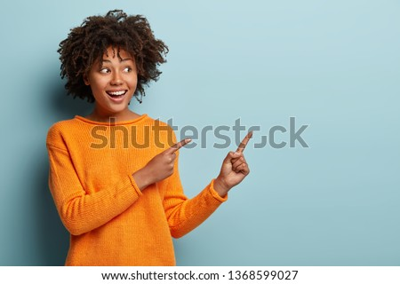 Horizontal shot pleased dark skinned female with Afro haircut, points away with both fore fingers, shows blank space for your promotion, isolated over blue background. People, advertisement concept
