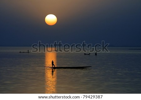 Horizontal silhouette of fishing canoes at sunset on Niger River in Mali