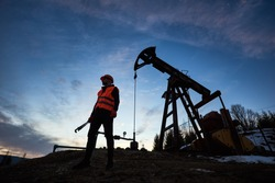 Horizontal snapshot of a silhouette of an oilman in orange vest and helmet, standing with his back to the oil pump jack in oilfield holding a pipe wrench, looking away, evening sky on background