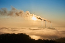 Horizontal snapshot of industrial area at setting sun, three smoking pipes from thermal power station pollute the atmosphere with black smog, concept of man-made disaster, environmental pollution