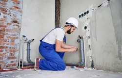 Horizontal snapshot of young plumber working with grey sewer pipes, fixing them to wall with a help of screwdriver. Side view of plumber standing on knees wearing blue uniform and white helmet