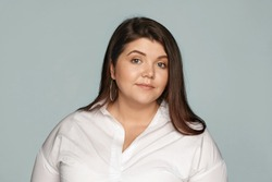 Horizontal studio portrait of adorable beautiful young overweight European woman with loose black hair and chubby cheeks wearing round earrings and xxl white shirt posing at blank wall, smiling