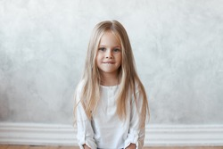 Horizontal studio shot of charming preschool girl with big blue eyes and long loose hair wearing stylish shirt, looking at camera and biting her lips. Adorable female child model posing indoors.