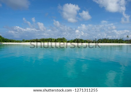 Horizontal symmetry image of Maldive island resort. White cloud sky, blue green sea water, green forest island in the middle of picture, a horizontal island,symmetrical