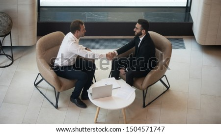 Horizontal top view european arabian businesspeople handshaking start meeting or accomplish negotiations feels satisfied, job interview process HR manager and applicant sitting on armchairs in office