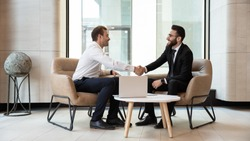 Horizontal view european and arabian businessmen in formal wear accomplish meeting shaking hands feels satisfied after negotiations, HR manager greeting applicant before job interview process concept
