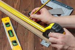 horizontal view from above of two hands using a pencil and a flexometer to measure the lenght of a wood strip on a set with others DIY tools
