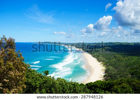 Horizontal view looking onto Tallow Beach in Byron Bay. The Pacific Ocean is a blue turquoise with white waves. The sand is golden, and the beach is surrounded by the green of Arakwai National Park. #287948126