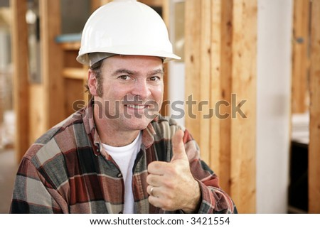 Horizontal view of a construction worker giving a thumbs up.  Authentic construction worker on actual construction site.  Room for text.