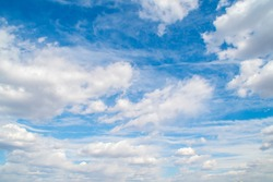 Horizontal view of a light, blue sky with white clouds. Airy, vibrant atmosphere