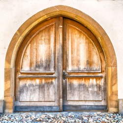 horizontal view of a massive winged wooden door in a stone wall with a wooden door arch