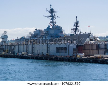 Horizontal view of a navy ship in for repair in Seattle Washington