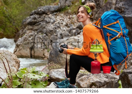 Horizontal view of cheerful pleased woman sits near rock pool, holds modern camera, prepares hot drink, enjoys camping and traveling, wears active wear, has rucksack on back. Rest, lifestyle, trekking #1407579266