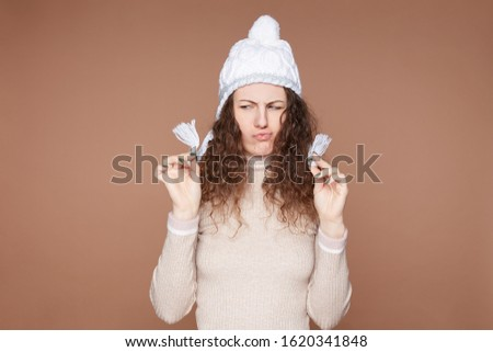 Horizontal view of dissatisfied curly haired female holds tails of knitted hat, demonstrates refusal gesture, not agree to wear lots of clothes, wears warm cashmere  jumper, poses on beige studio wall